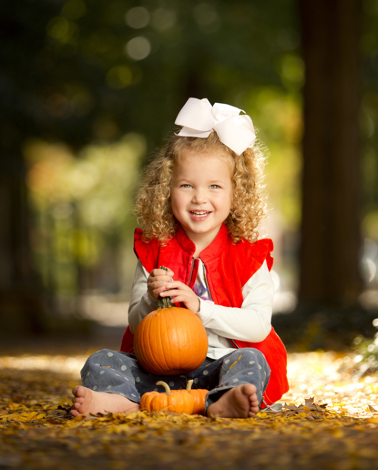 girl sitting on sidewalk with pumpkin